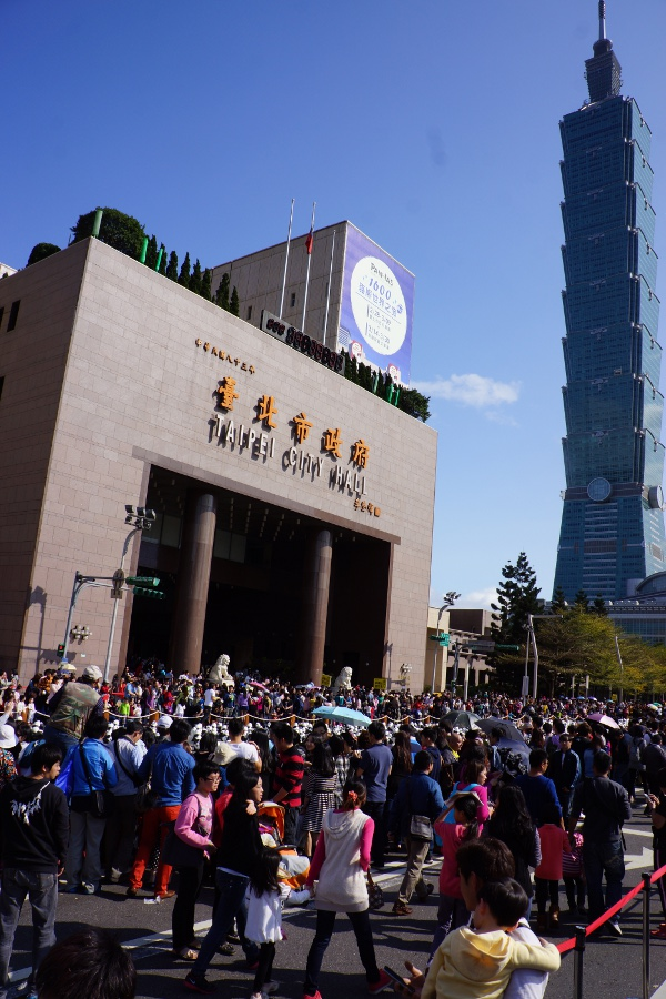 People crowd around the pandas on a clear day.