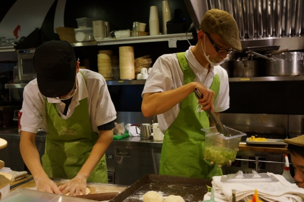 One chef rolls bread while the other gets the toppings ready.