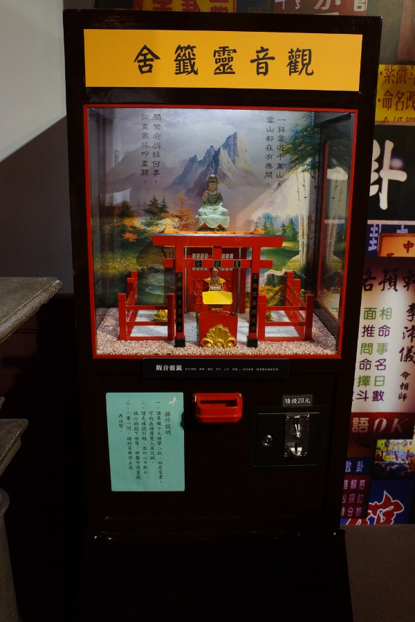 In this fortune telling game, the figure at the bottom backs into the temple, then reemerges with a scroll dictating your fortune, which drops down into the bottom tray.