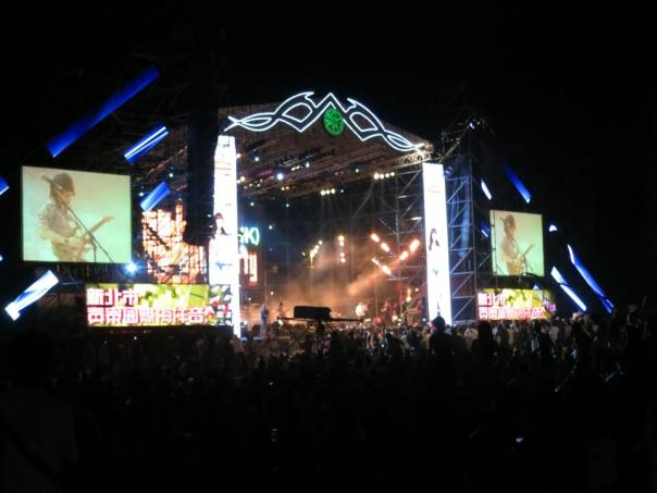 A wide shot of the stage at night.  The green logo in the middle changes colors.