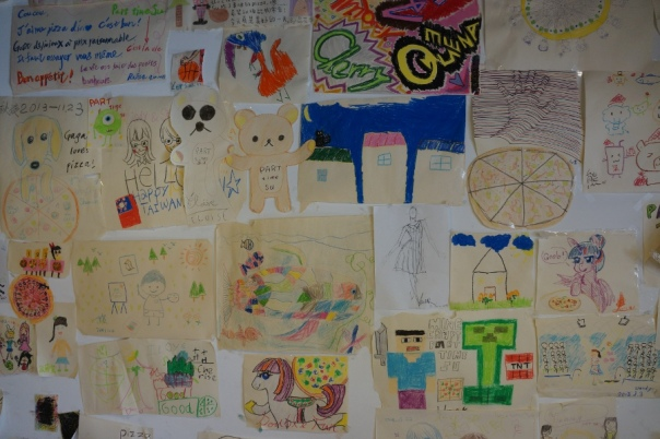 Kids' drawings cover one side of the wall.