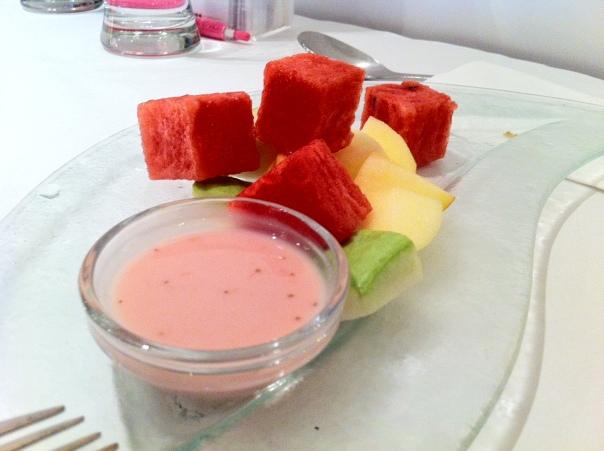 Sliced fruit with strawberry yogurt.