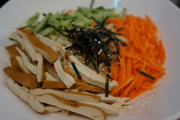 Noodles are hiding under the carrots and tofu.